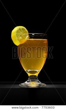 Orange juice glass with lemon on black