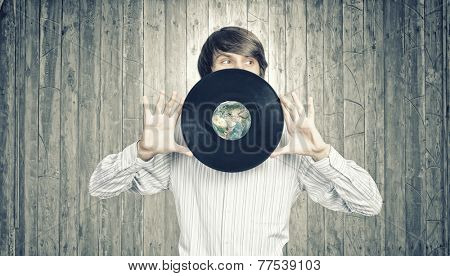 Young handsome man dj holding disco plate Elements of this image furnished by NASA