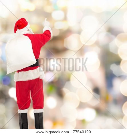 christmas, holidays and people concept - man in costume of santa claus with bag pointing finger from back over yellow lights background over lights background