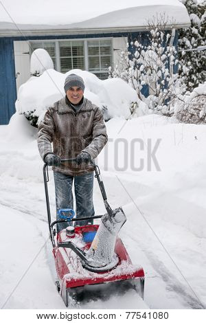 Man using snowblower to clear deep snow on driveway near residential house after heavy snowfall.