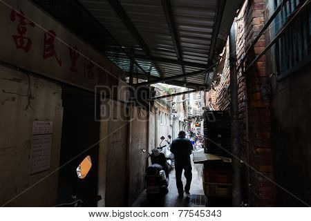 TAIPEI, TAIWAN - November 16th : Someone walk through a narrow alley near Longshan Temple, Taipei, Taiwan on November 16th, 2014.