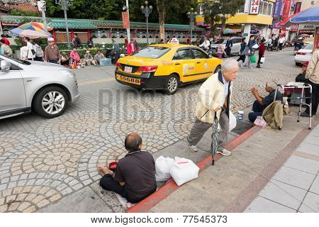 TAIPEI, TAIWAN - November 16th : Pedestrian and beggar out of the Longshan Temple, Taiwan on November 16th, 2014.