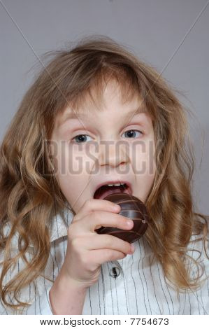 A Little Girl Biting Chocolate Coated Cookie.