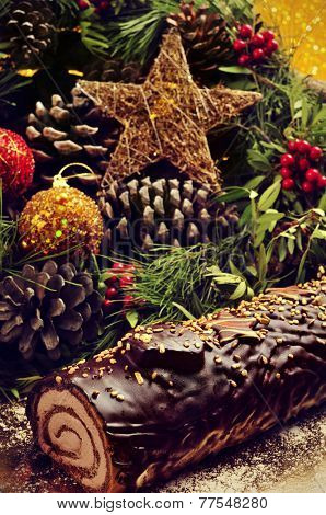 closeup of a yule log cake, traditional of christmas time, on a table ornamented with christmas balls and satrs, and natural ornaments