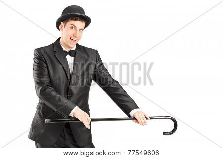 Male magician holding a cane isolated on white background
