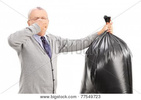 Senior carrying a stinky garbage bag isolated on white background