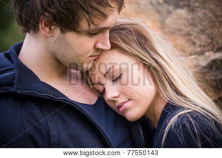 Romantic, tender moment of a young attractive couple. Adorable girl closing her eyes on her boyfriend