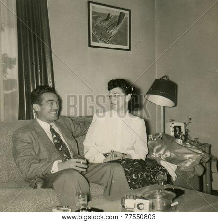 CANADA - CIRCA 1950s: An antique photo shows portrait of a man and woman in the interior of their apartment.