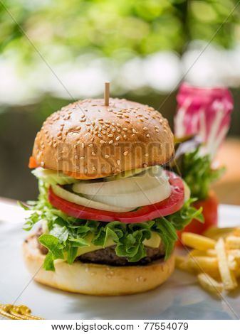 Classic deluxe cheeseburger with lettuce, onions, tomato and pickles on a sesame seed bun. Macro with shallow dof.