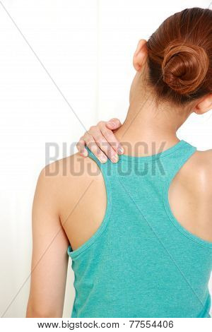 back shot of woman suffers from stiff neck