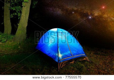 Tourist tent in nighty forest on sky background