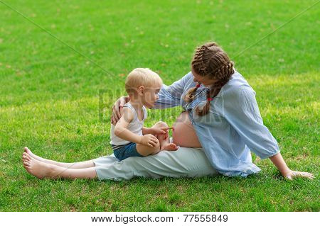 Pregnant woman and her son 2 yo outdoors