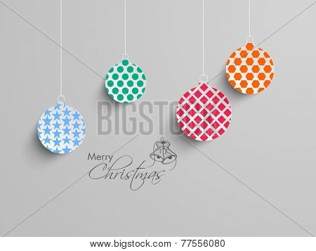 Merry Christmas celebration with stylish and colorful X-mas balls hanging on grey background.
