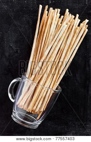 breadsticks grissini torinesi in glass cup on blackboard background