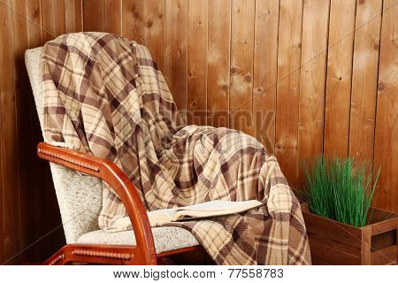 Rocking chair with plaid near wooden wall