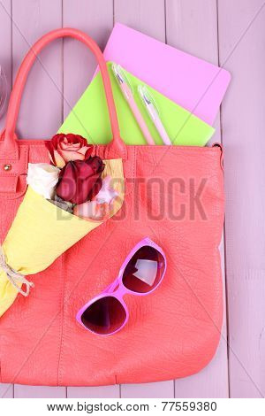 Women bag stuff on wooden background top view