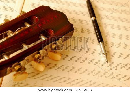 Closeup Of Guitar With Pen On Music Manuscript
