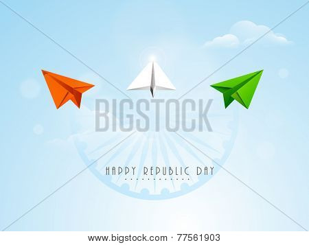 Flying paper plane in national tricolor with Ashoka Wheel on cloudy blue background for Indian Republic Day celebration.