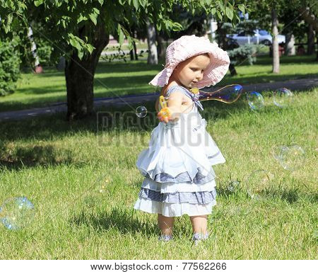Little girl blowing soap bubbles in a city park.