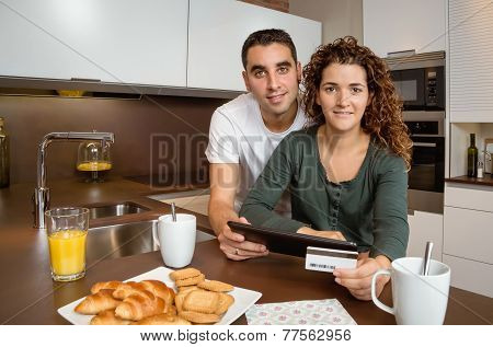 Couple with electronic tablet and credit card buying online