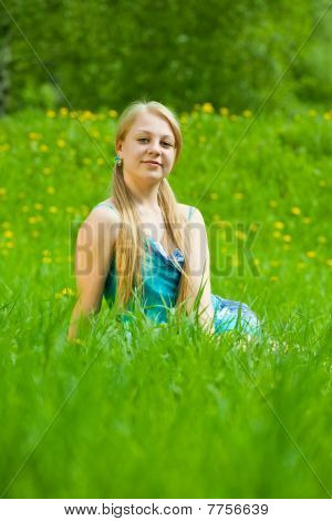 Blonde Girl Relaxing In Grass