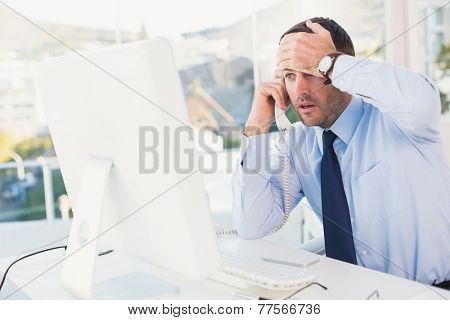 Shocked businessman on phone at his desk in his office