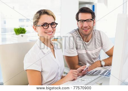 Smiling photo editors looking at camera in their office