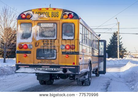 A typical yellow school bus stopped to pick up passengers on an extremely cold winter day.