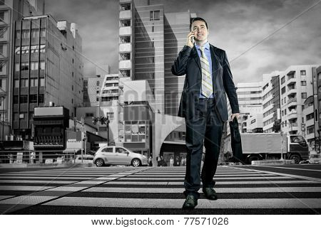 Businessman speaking by phone on the crossroad