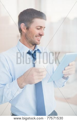 Smiling businessman using tablet holding disposable cup seen through window in his office