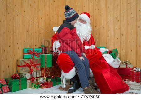 A boy visiting Santa in his grotto at Christmas.