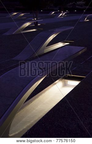 ARLINGTON, VA - SEPT 13, 2014: Lighted pools of flowing water glow under the granite cantilevered bench memorial units made for each victim of the Sept 11, 2001 attack at the Pentagon.