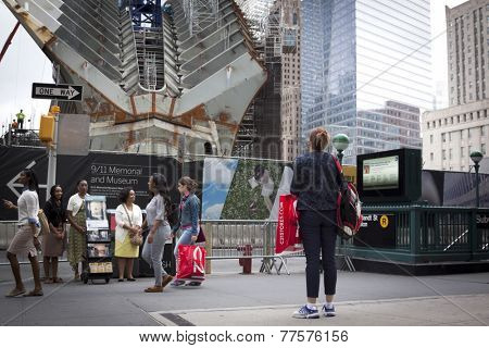 NEW YORK - SEPT 11, 2014: A woman stops and silently looks towards the World Trade Center site while others pass by at 9:59 a.m., the time when the South tower collapsed.