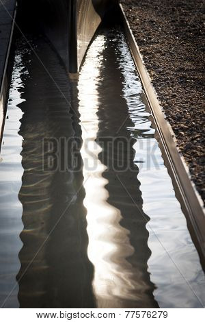 ARLINGTON, VA - SEPT 13, 2014: A lighted pool of water under the granite and stainless steel cantilevered bench memorial unit at the Pentagon Memorial.