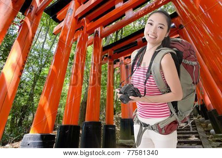 Happy smiling Asian young female backpacker with camera in Fushimi Inari Taisha, Japan.
