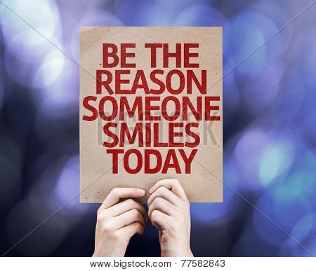 Be The Reason Someone Smiles Today card written on colorful background with defocused lights