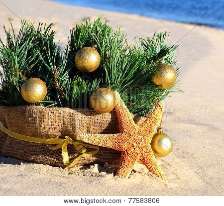Christmas Tree With Golden Christmas Balls And Starfish On The Sand On The Beach
