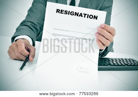 a man in suit in his desk showing a figured signed resignation document