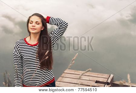 Cute Attractive Young Woman Enjoying Harmony Of Nature On Pier Near The Lake