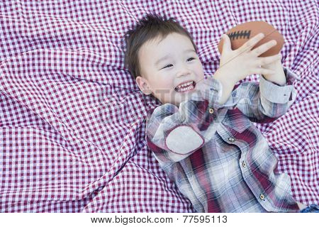 Cute Young Mixed Race Boy Playing With Football Outside On Picnic Blanket.