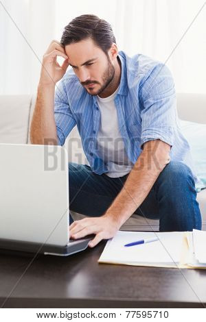 Worried man sitting at table using laptop to pay his bills in the living room