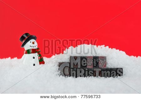 The words Merry Christmas in old letterpress surrounded by snow and a snowman, red background.