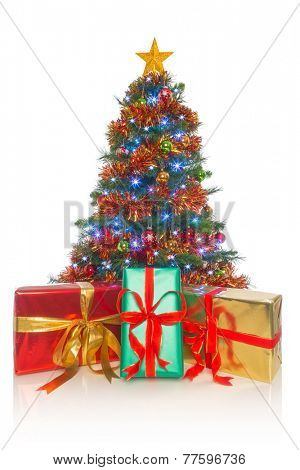 A decorated Christmas tree with gift wrapped presents in front isolated on a white background.