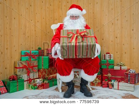 Santa Claus / Father Christmas sitting in his grotto holding a gift wrapped present for you.