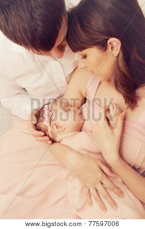 Happy Family Of Two Holding Cute Sleeping Newborn Baby Girl