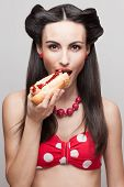 foto of pinup girl  - Skinny beautiful girl eating hotdog - JPG