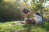 stock photo of brunette hair  - woman lying on bedding on green grass with ipad during picknic in the park - JPG