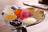 stock photo of english rose  - Delicious butter scones on a silver heart shaped tray served with roses cheese cream and jam preserves on a wooden table - JPG