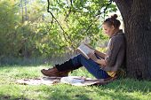 picture of knitwear  - Young woman reading book under the tree during picnic in evening sunlight - JPG