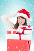 foto of scratching head  - Attractive santa woman scratching head and holding gifts against blue vignette - JPG